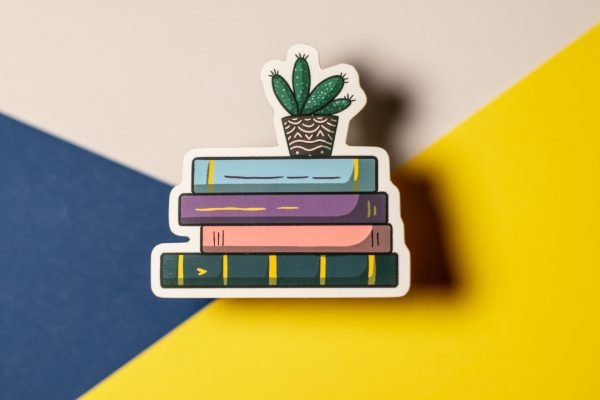 pastel stack of books on tri-colored background