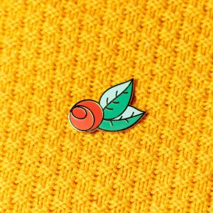red rose hard enamel pin on yellow knit