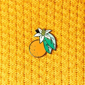 orange blossom hard enamel pin on yellow knit