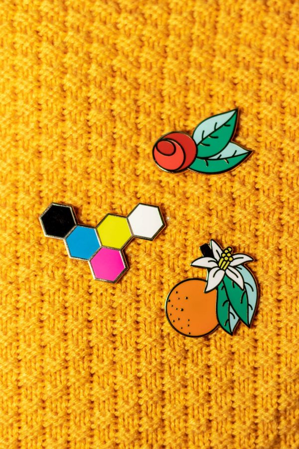 orange bollsom, red rose, and hex enamel pin on yellow knit
