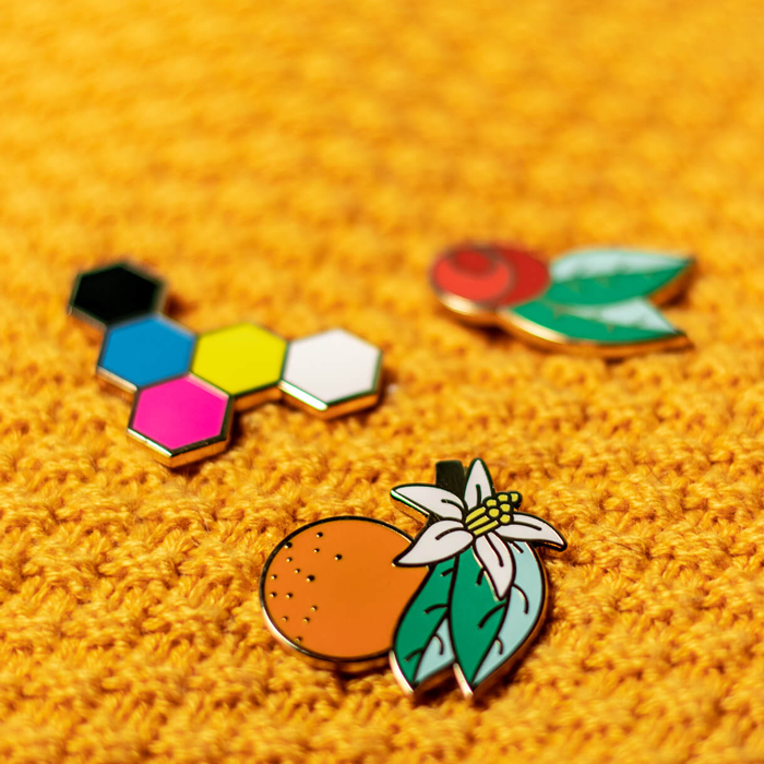 orange blossom, red rose, and CMYK Hex hard enamel pin on yellow knit